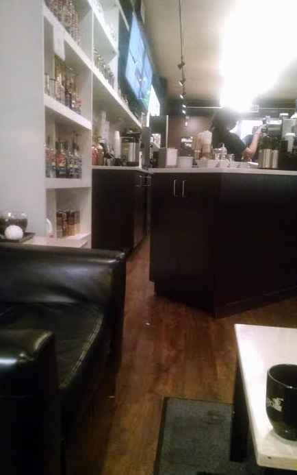the decor is a little industrial but very welcoming with dark wood tables leather couches and a marble countertop